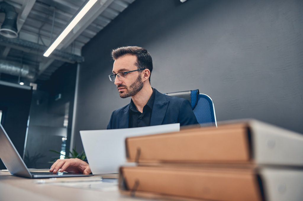 Financial accountant working on the laptop at the office desk